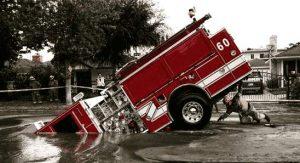 Feuerwehrauto im großen Straßenloch