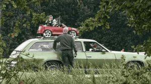 Kleines Auto mit Kind auf dem Dach