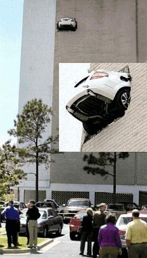 Auto hängt in der Wand eines Hochhauses